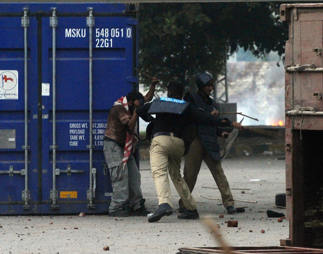 A Pakistani policeman beats a Muslim demonstrator during a protest against an anti-Islam film in Lahore.