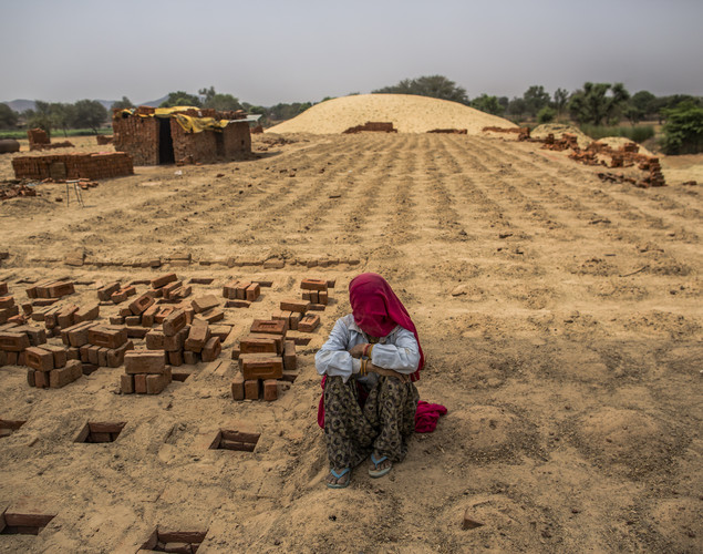 A woman takes a break from stacking baked bricks at a brick making facility on May 23, 2012 in a village near Jaipur, India.