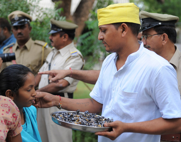 An Indian inmate of Sabarmati Central Jail offer sweets to little guests at Sabarmati Central Jail after a flag hoisting ceremony to celebrate India's Independence Day at the Sabarmati Central Jail in Ahmedabad on August 15, 2012.