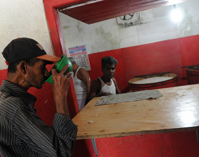 A customer drinks palm wine, or toddy as it is locally known, at a shop in Aluthgama.