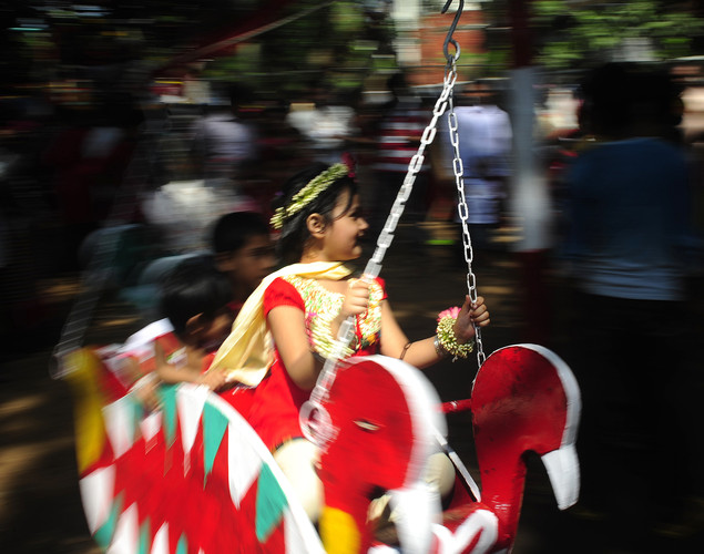 "A Bangladeshi child rides a merry-go-round at a rally in celebration of the Bengali New Year or ""Pohela Boishakh"" in Dhaka."