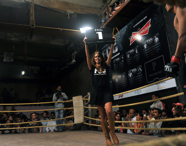 A girl carries a placard signalling the start of round one during a bout at the FCC (Full Contact Championship) 6 fight night in Mumbai.
