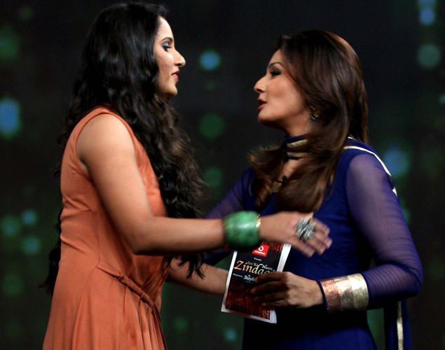 "Indian tennis player Sania Mirza (L) interacts with Bollywood actress Raveena Tandon on the set of NDTV's television show ""Issi Ka Naam Zindagi"" in Mumbai."