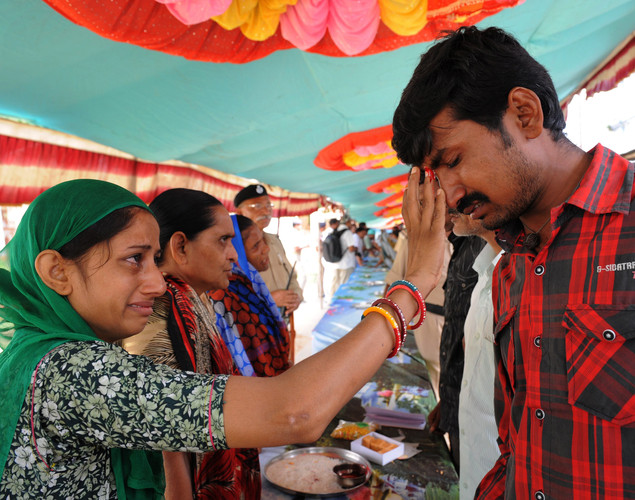 An Indian inmate of the Sabarmati Central Jail (L) reacts as she applies a Tilak on the forehead of her brother after tying a rakhi bracelet to his wrist during the Raksha Bandhan festival in Ahmedabad.