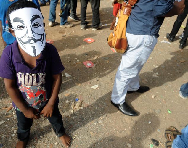 A street child wears a mask at the site of a rally by the group Anonymous as they protest against the Indian Government's increasingly restrictive regulation of the internet in Kolkata.