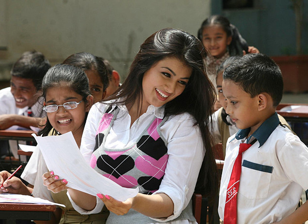 Ayesha Takia (C) interacts with children while on location for the Hindi film 'Paathshala' in Mumbai on March 27, 2010.