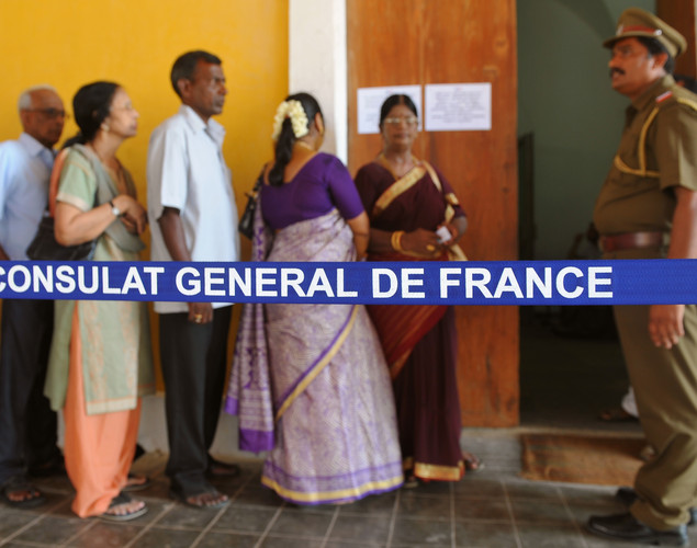 Indo-French citizens stand in line at a polling station in Pondicherry on April 22, 2012, prior to casting their votes during the first round of French presidential elections.