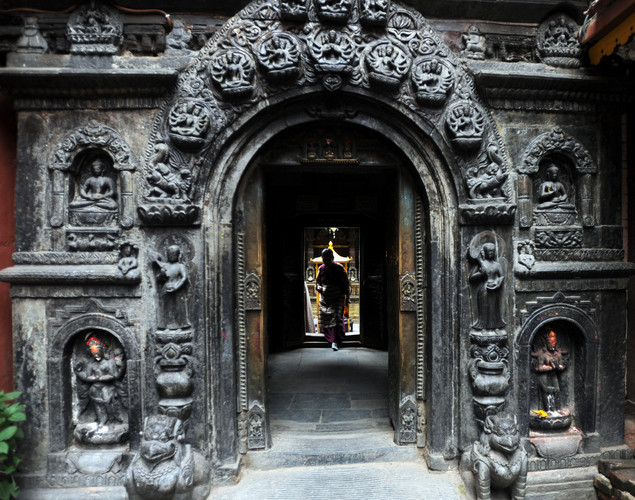 A Nepalese woman leaves the Golden temple near Patan durbar square in Lalitpur on August 3, 2011. The Golden Temple was founded during the 12th Century near Patan Durbar Square, a UNESCO World Heritage Site,famous for fine ancient art, making of metallic and stone carving statues.