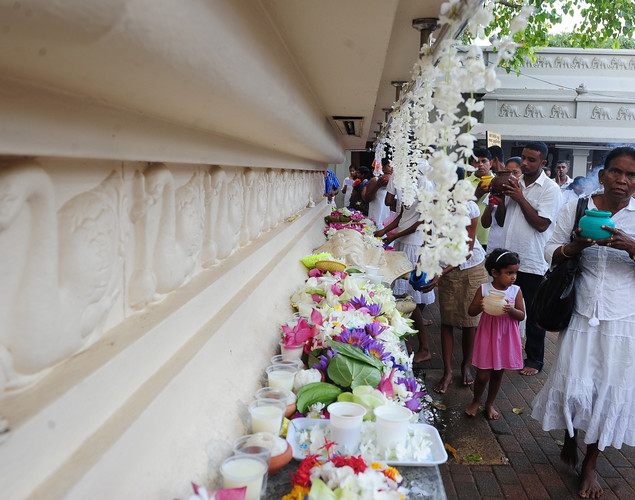 Sri Lankan Buddhists hold pots of water during prayers for Vesak at the Temple in Colombo.