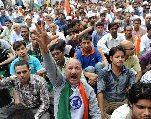 Indian supporters of anti-corruption activist Anna Hazare shout slogans during a protest in New Delhi .
