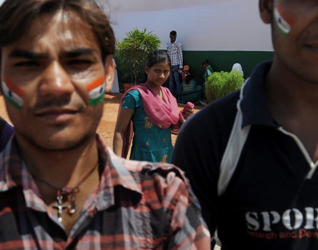 An Indian woman watches Indian men pose for a photograph at the India Gate monument in New Delhi during Independence day celebrations on August 15, 2012.