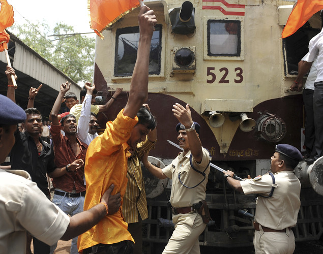 Indian railway police attempt to detain Shiv Sena party workers as they protest on a railway track during a nationwide strike in Mumbai.