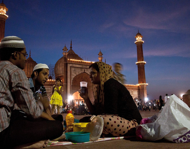 An Indian Muslim family breaks their fast during sunset on the first day of the fasting month of Ramadan at the Jama Masjid Mosque in New Delhi.