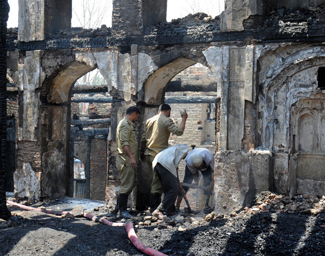 Fire services personnel and volunteers clear debris inside the charred remains of the 200-year old shrine of Sheikh Abdul Qadir Jeelani, also known as Dastigheer Sahib, in downtown Srinagar.