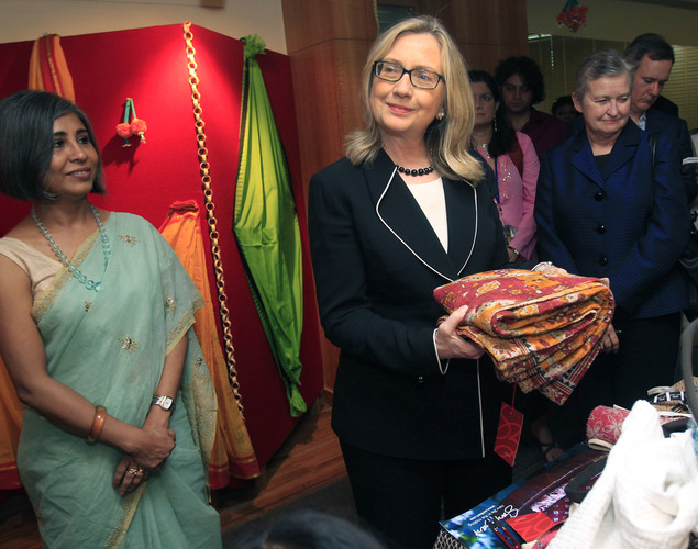 Us Secretary of State Hillary Clinton (C) holds a sari during an Anti-Human Trafficking event in Kolkata.